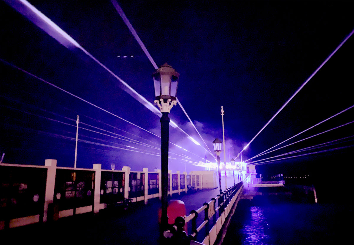 A photograph of Worthing pier at night with laser beams emanating from the pavilion into the sky